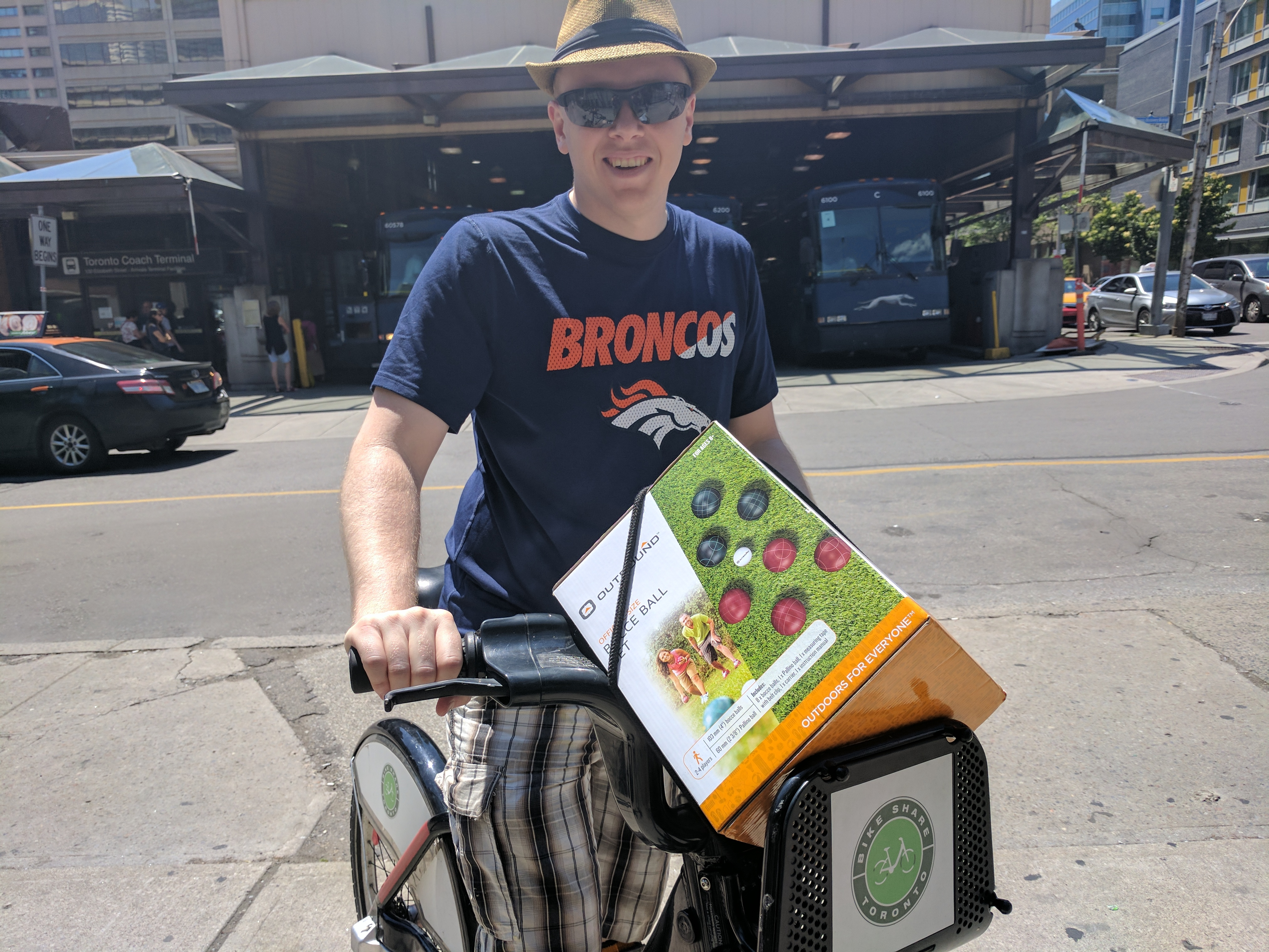 person standing with a Bike Share Toronto bike with bocce balls in the basket