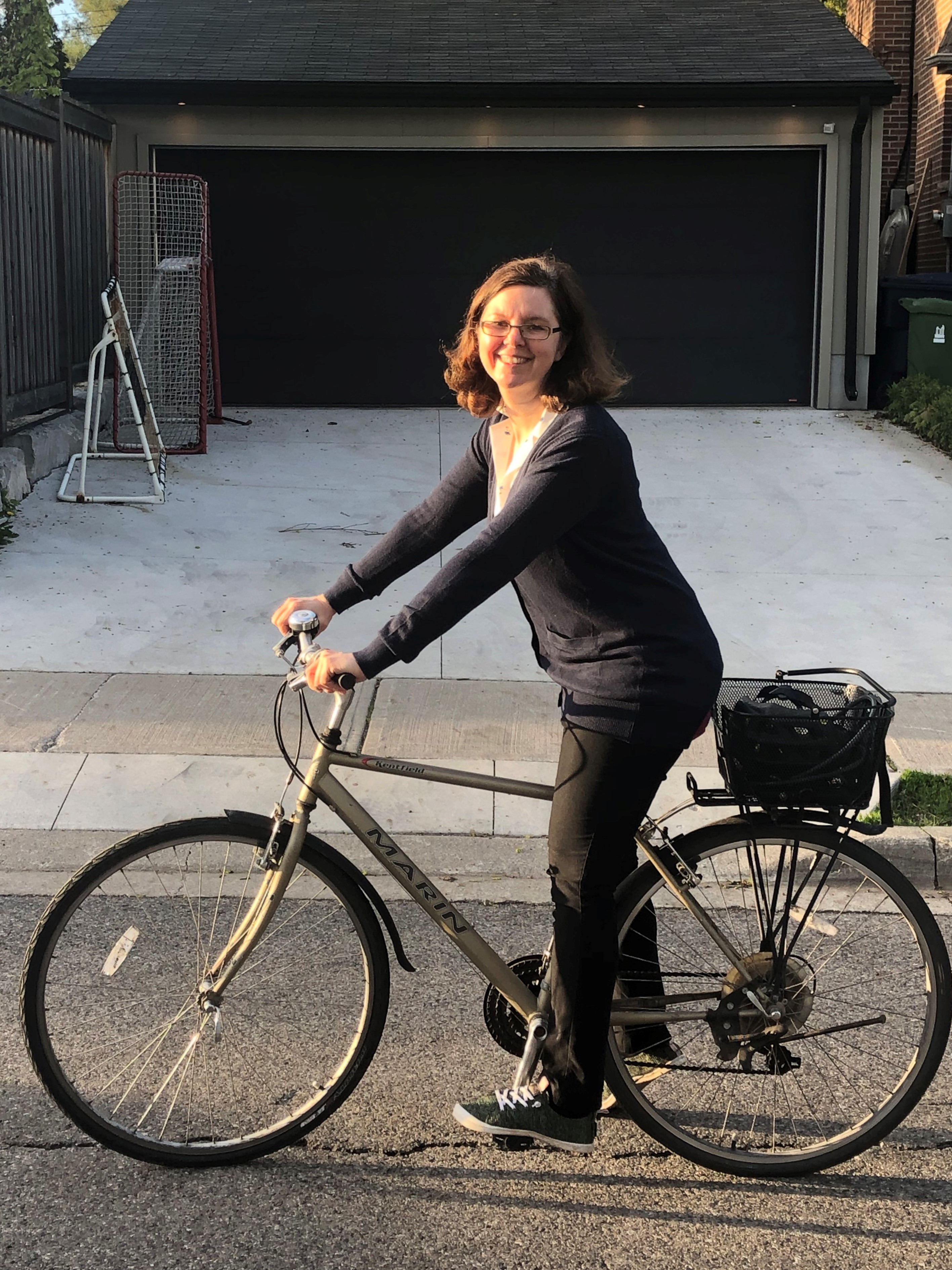 Woman on a bike in front of a driveway
