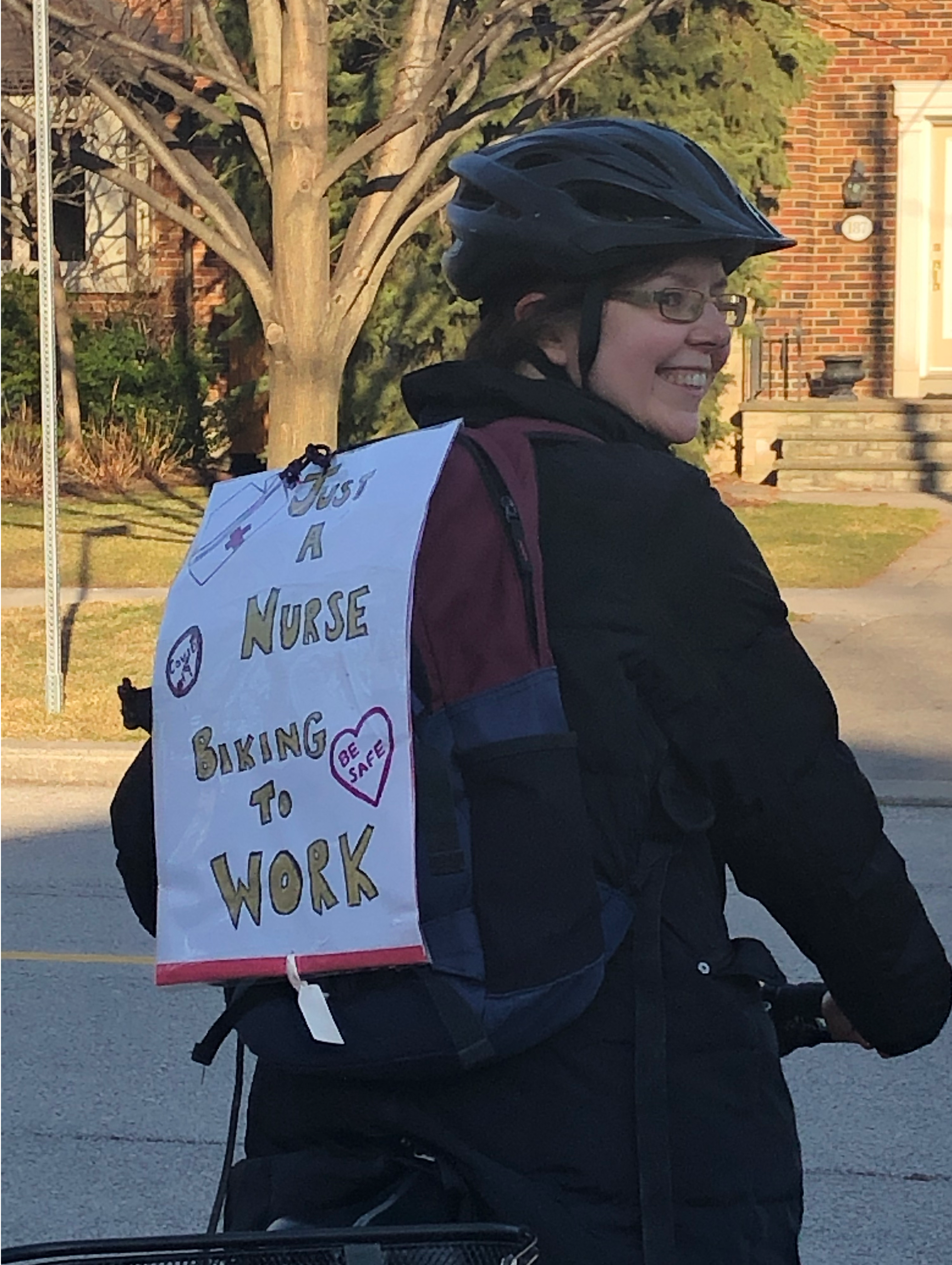 """Smiling person on bike wears a sign that says """"Just a nurse biking to work"""""""