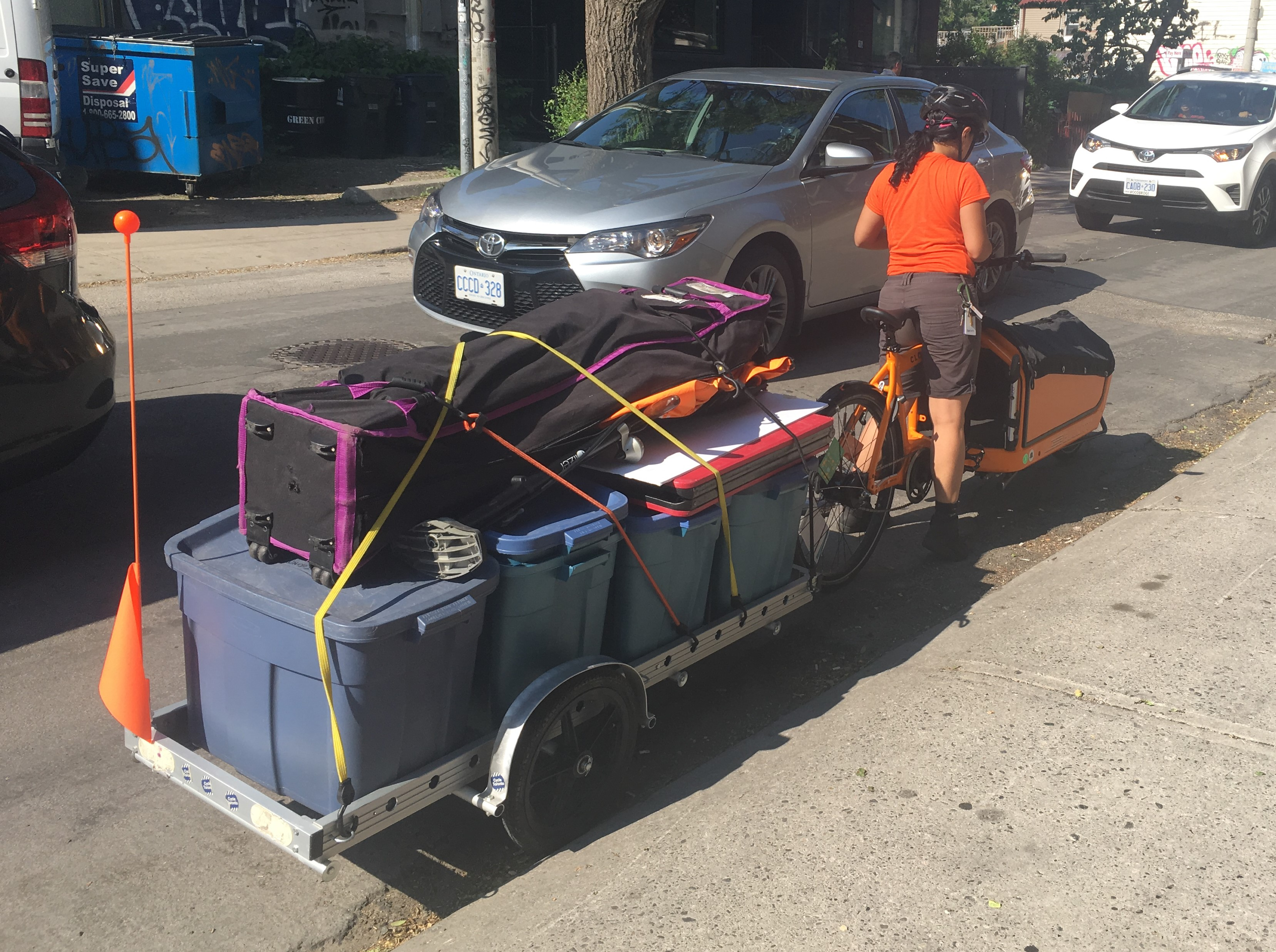 Cargo bike and trailer loaded up with several plastic crates