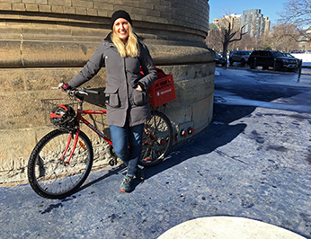 Léa posing with her bike on King's College Circle at U of T