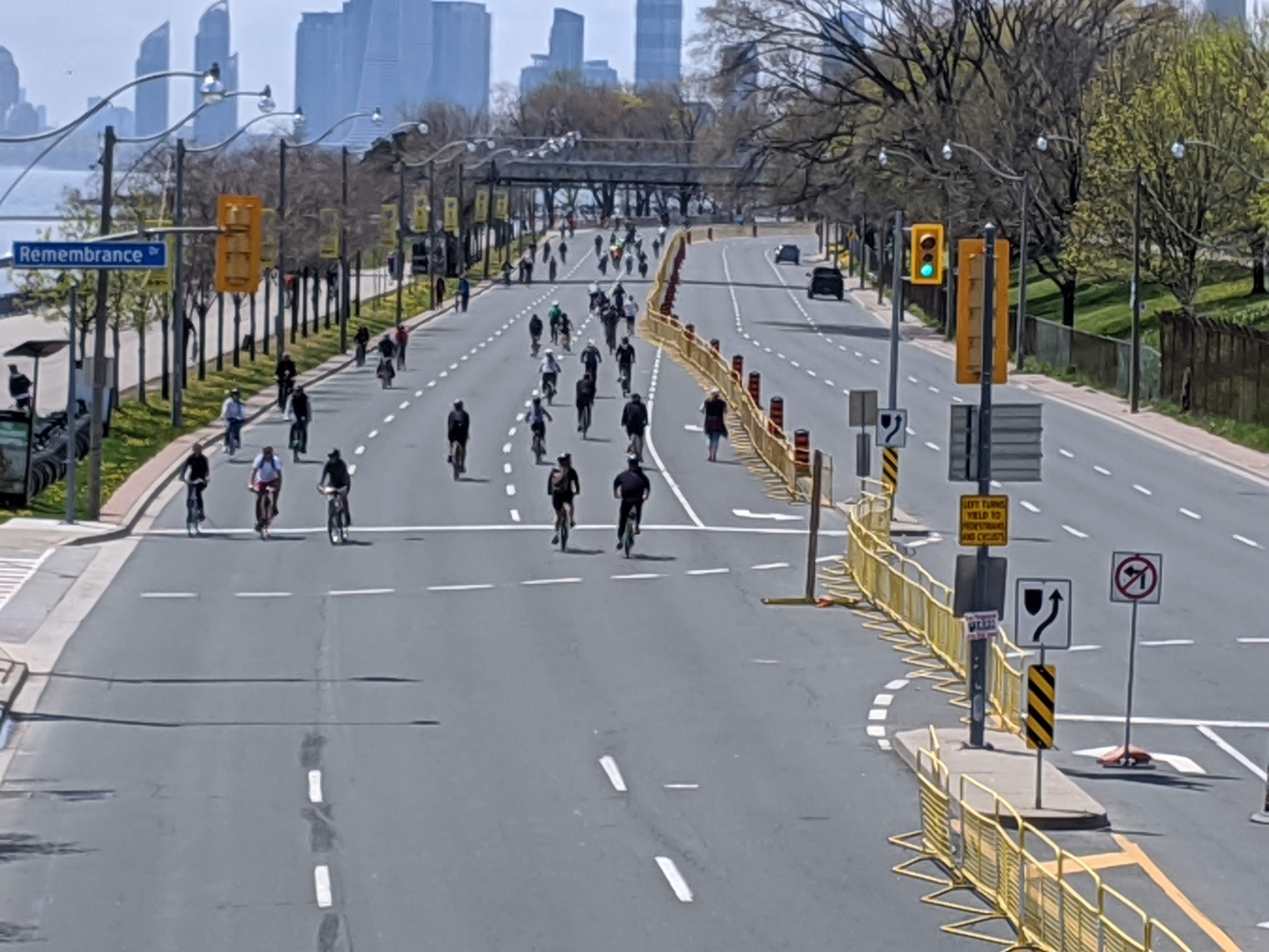 Wide street with many people walking, biking and running on it