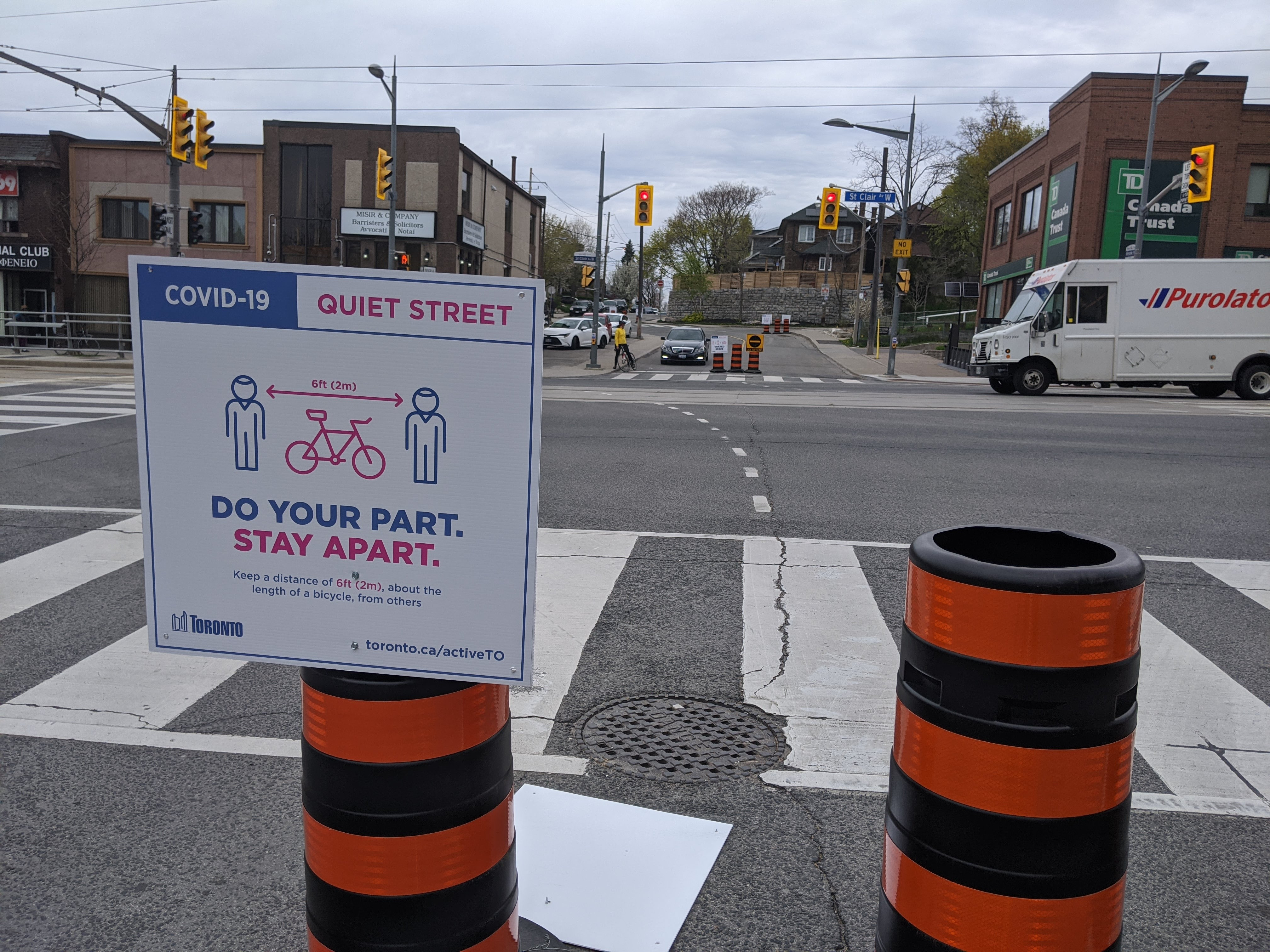 Sign and orange barrels in middle of street indicate that it is a Quiet Street for sharing