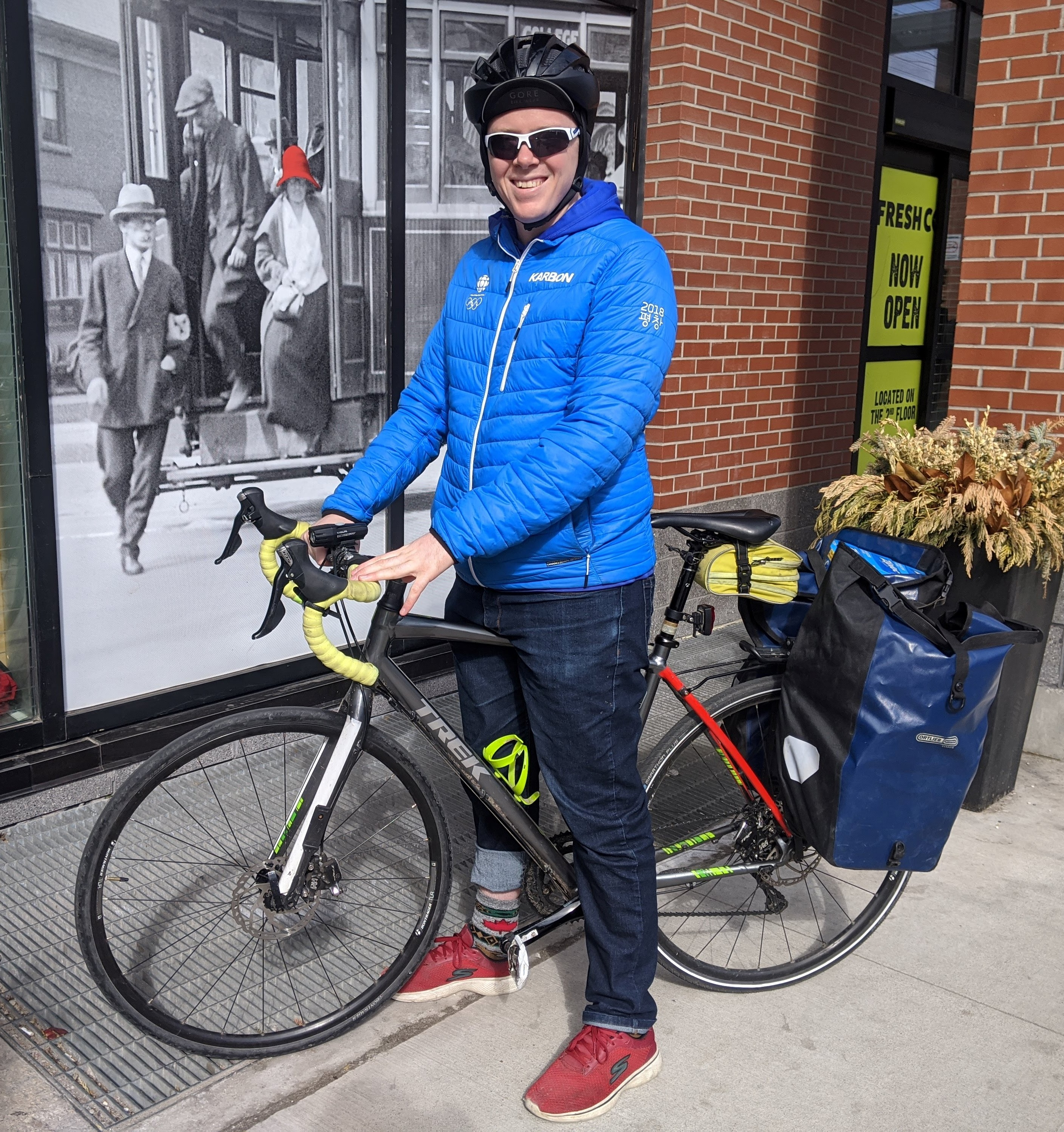 Person in jacket with bike loaded with groceries