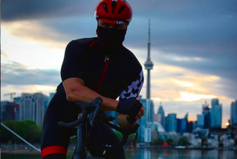 A person in black and red cycling kit with their face covered leans on their bike in front of a moody Toronto skyline.