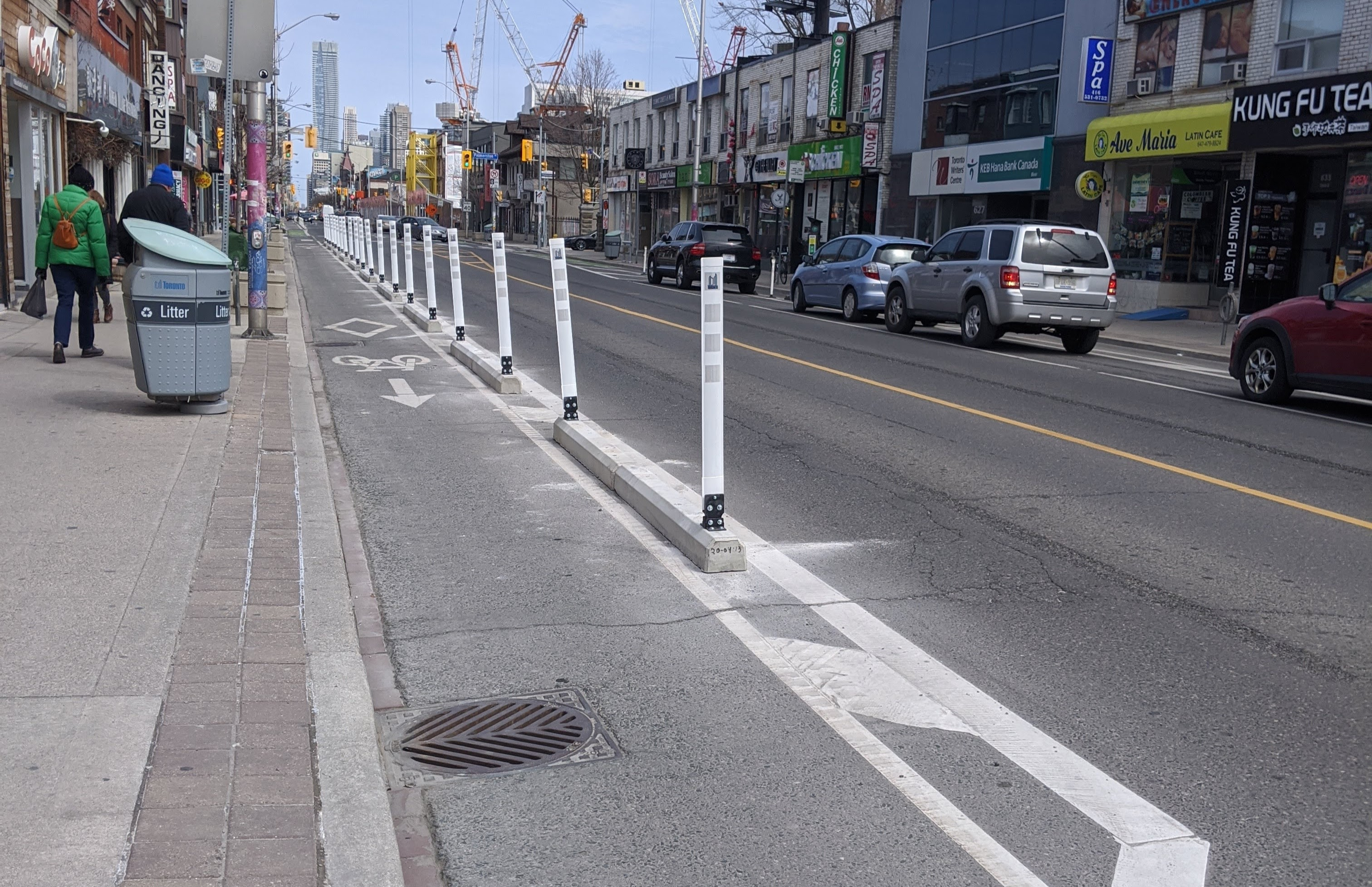 Curbs with bollards on top separate a bike lane from a busy street