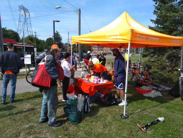 People with bikes surround an orange tent with information pamphlets. They are wearing masks, but clearly talking.