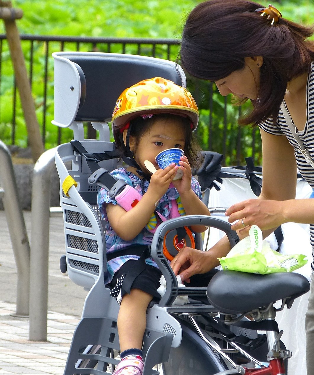A child sits in a rear child seat while eating a tasty treat. An adult leans over them.