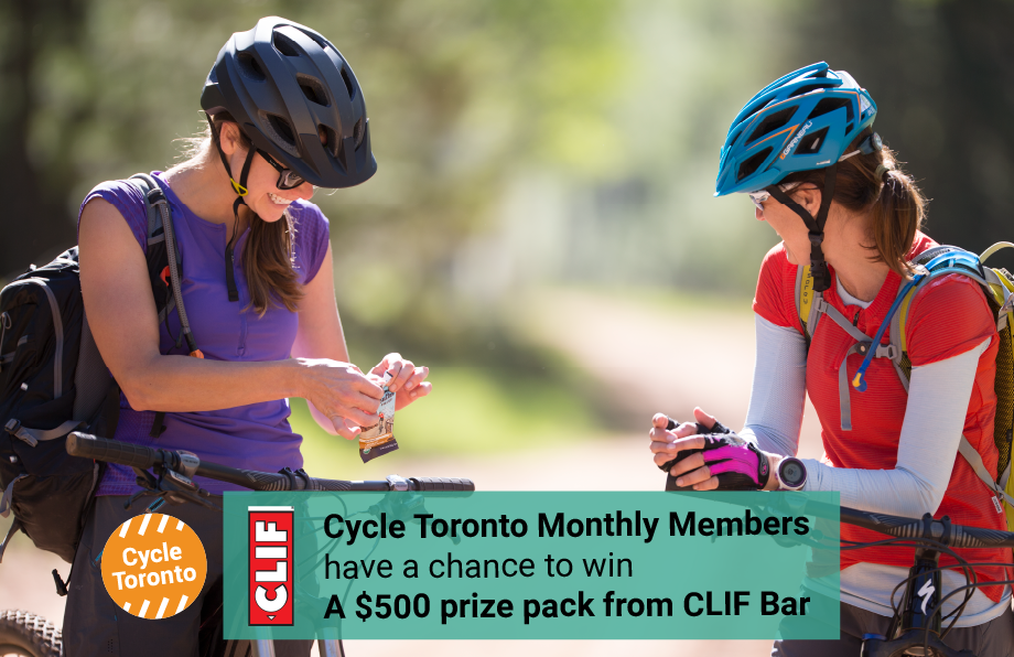 Two people enjoy CLIF bars on their bikes. Cycle Toronto Monthly Members have a chance to win a $500 gift pack from CLIF bar