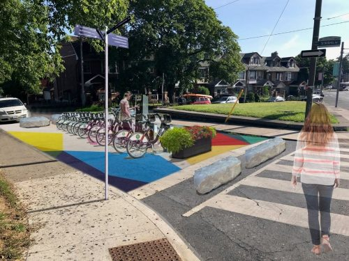 Artist rendering of car-free Saint Helens Ave with parkette and bike share station.