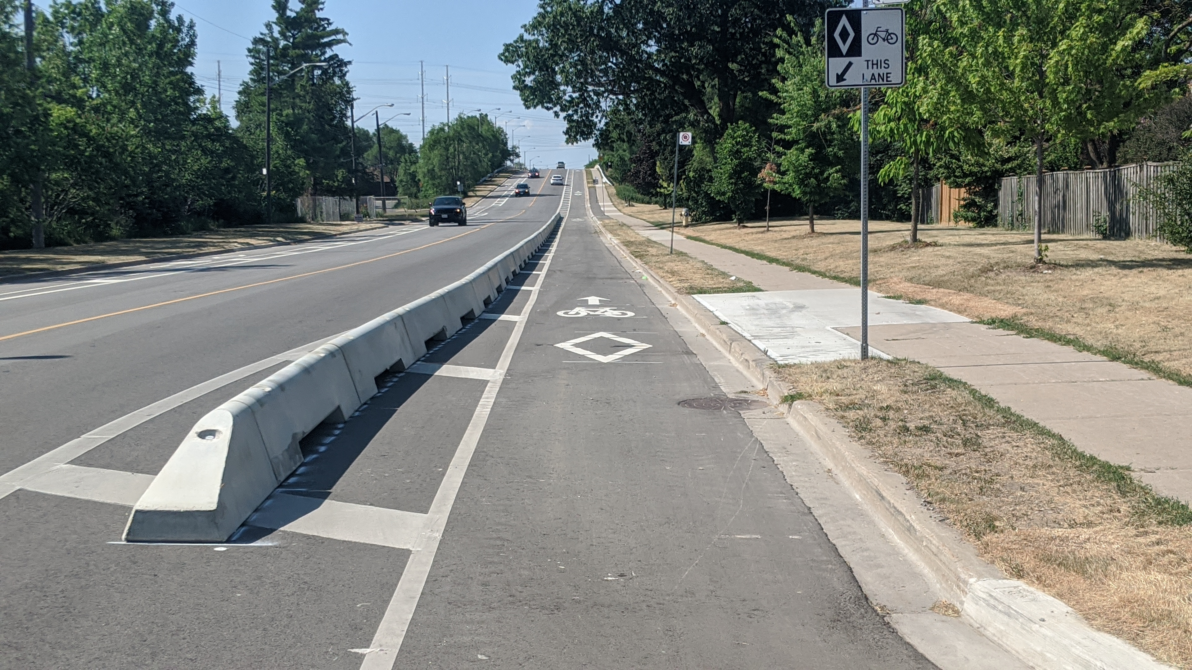 A wide road crests a hill in the distance. In the foreground a grey concrete wall separates a bike lane from traffic.