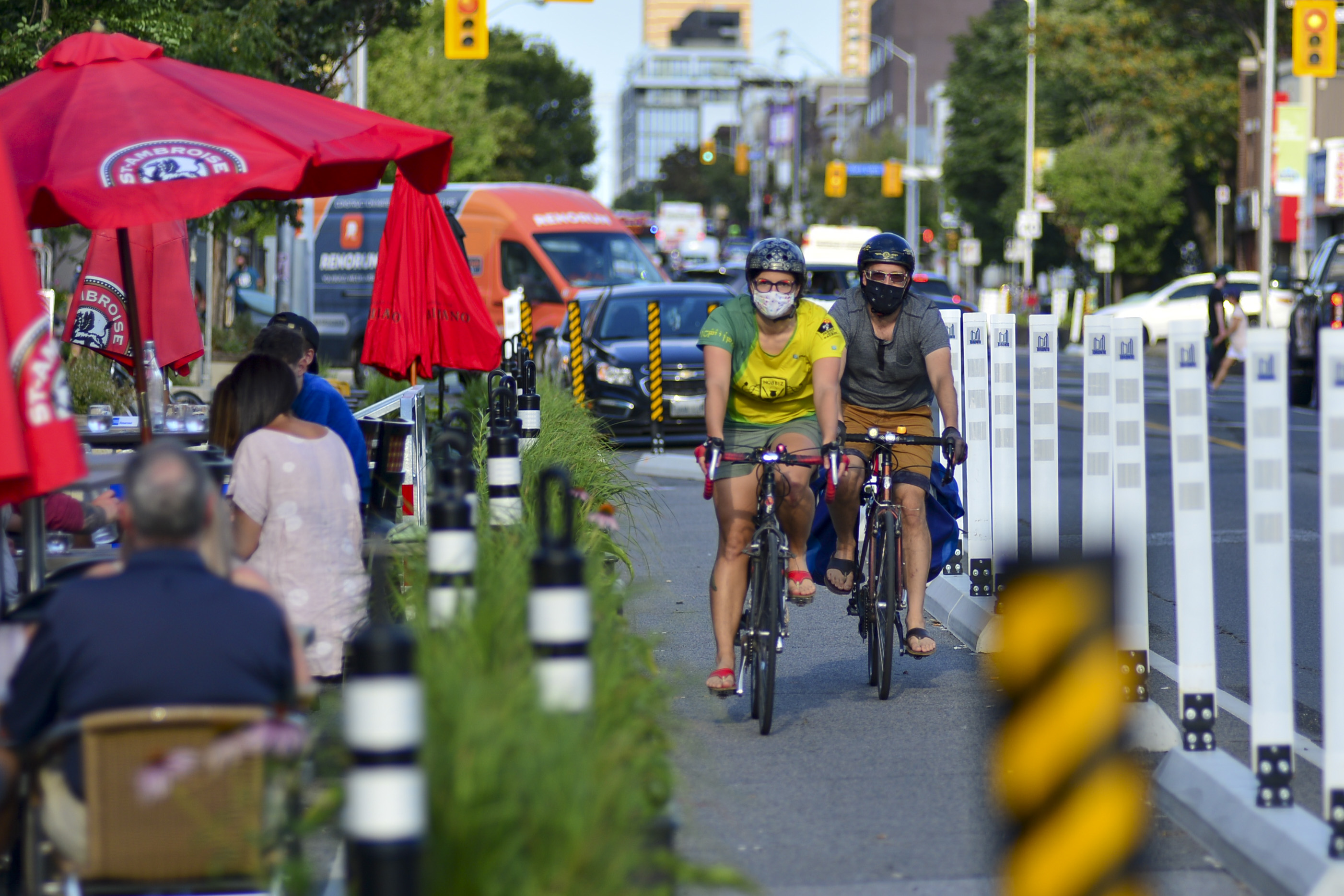 People wearing masks ride bikes past a patio.