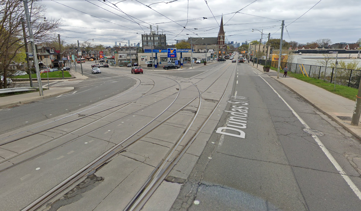 College and Dundas intersection. Streetcar tracks cut down the middle of a complicated intersection with a bike lane.