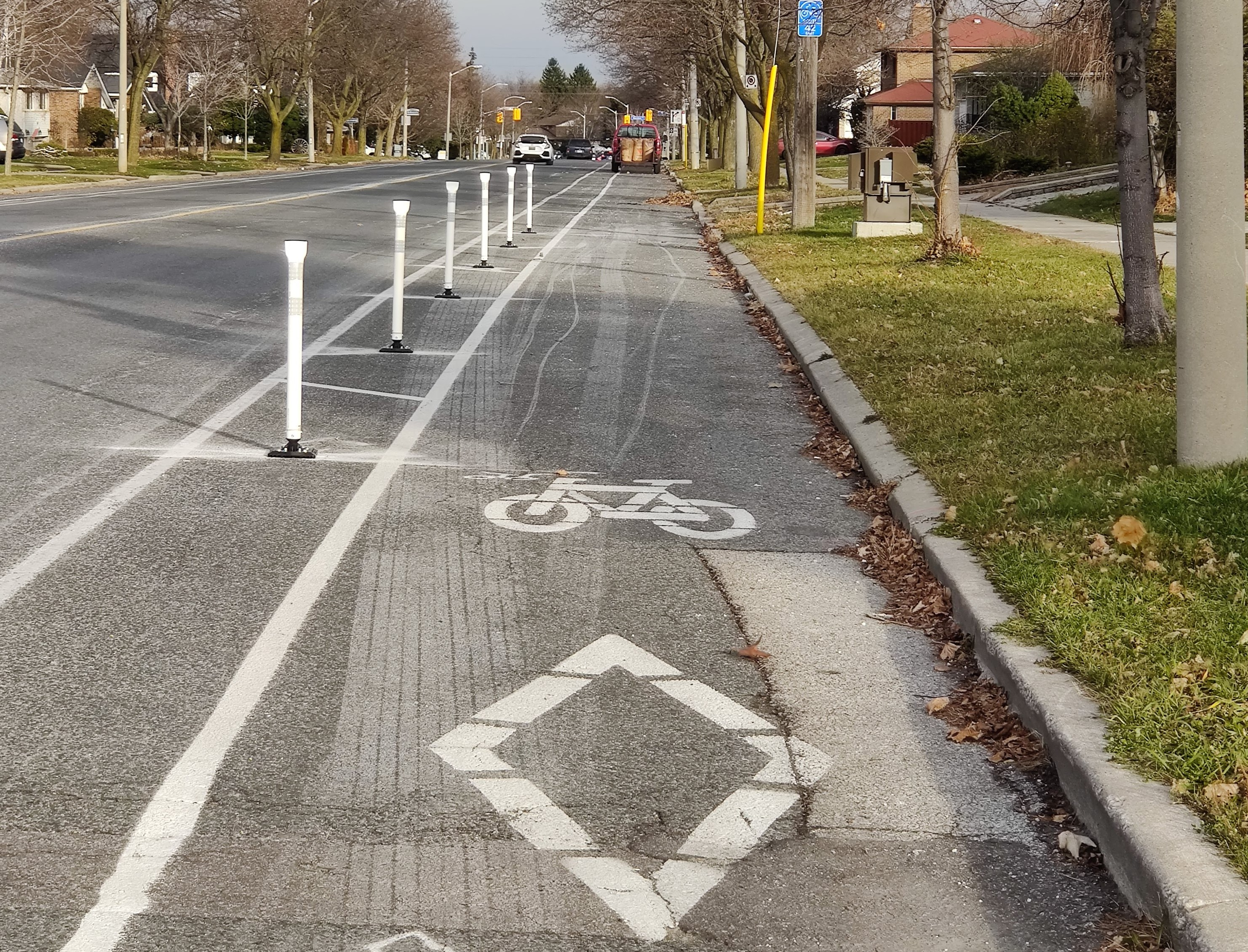 Flexi-posts line a bike lane. In the distance, after the flexi-posts end, a vehicle is parked in the bike lane.