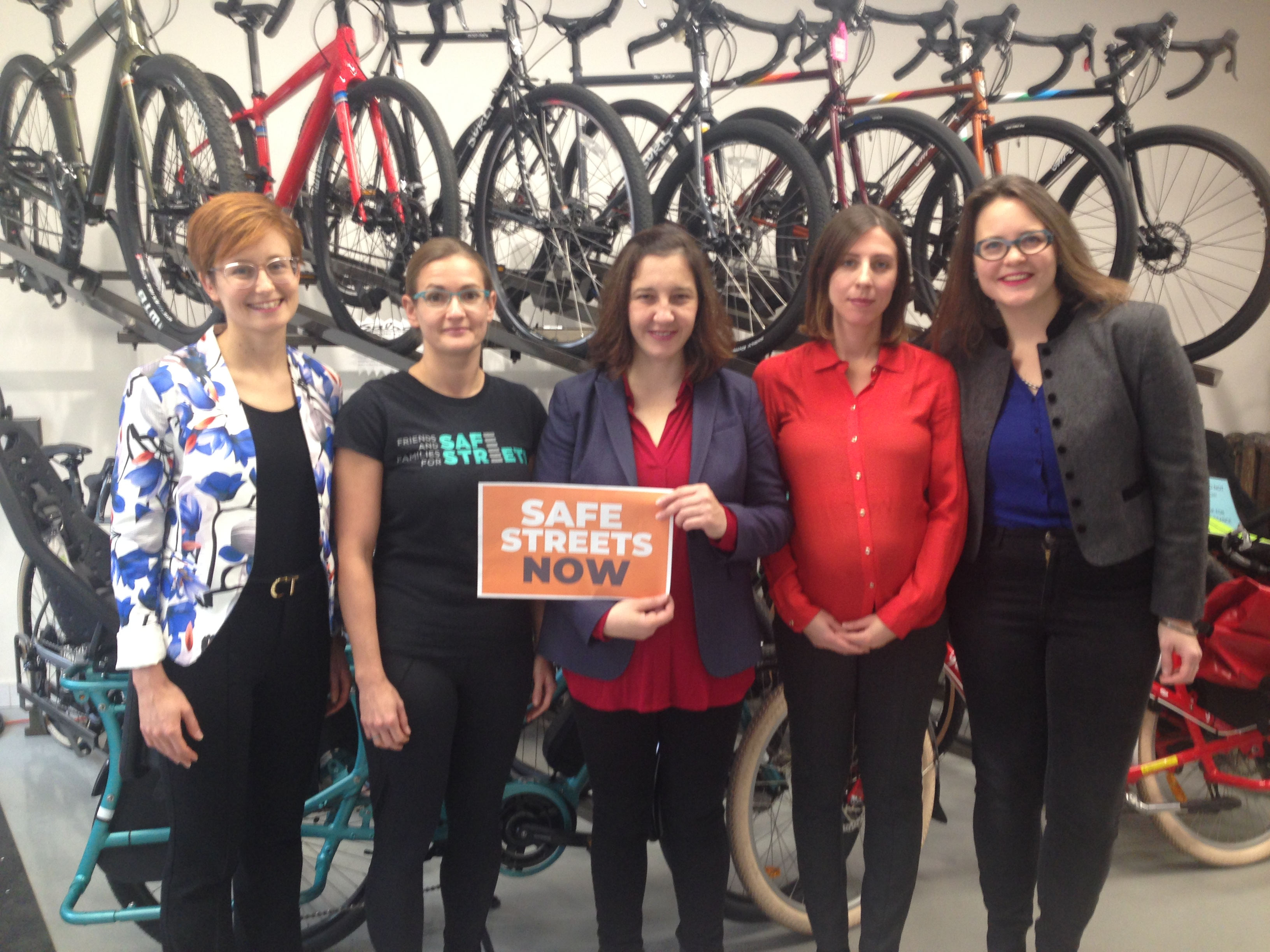 """Keagan Gartz stands with MPP Jessical Bell and other supporters in a bike shop holding a sign """"Safe Streets Now"""""""