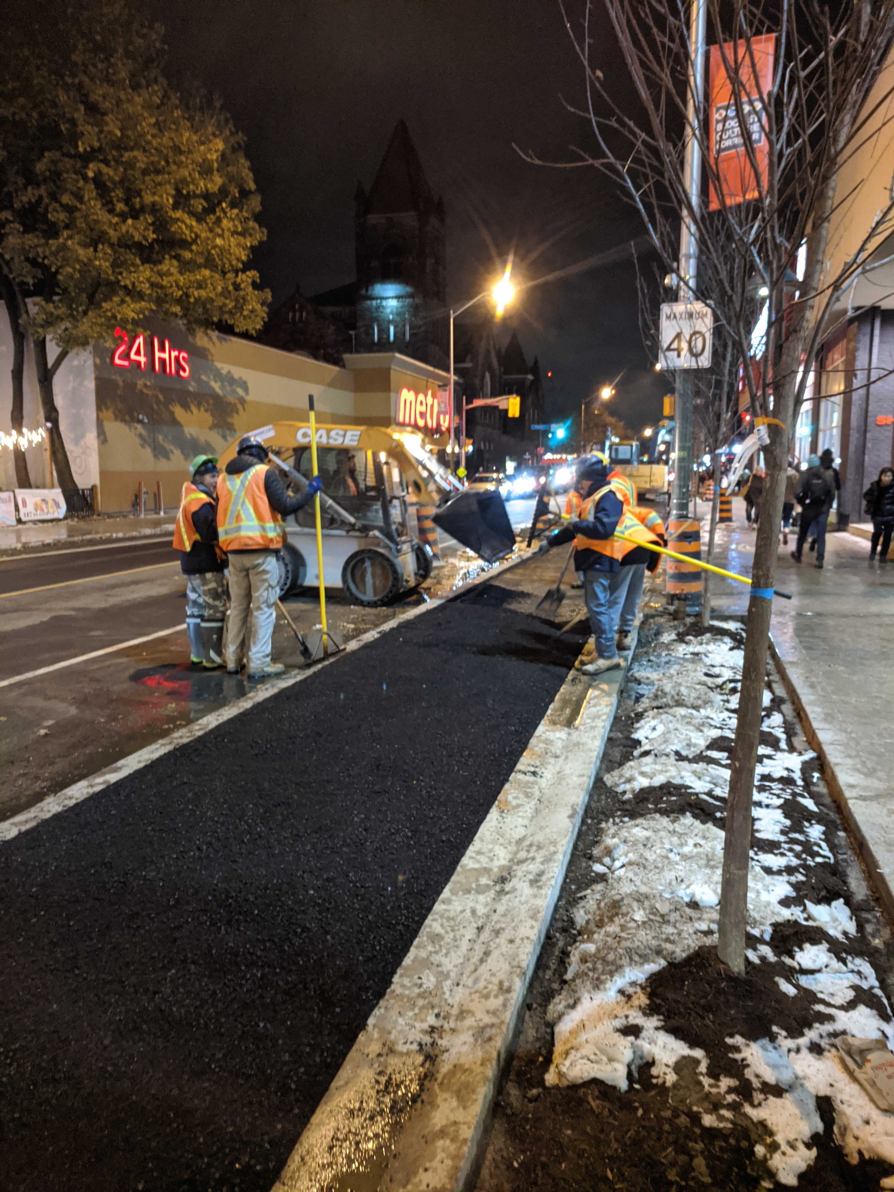 Construction workers laying asphalt on Bloor cycle track