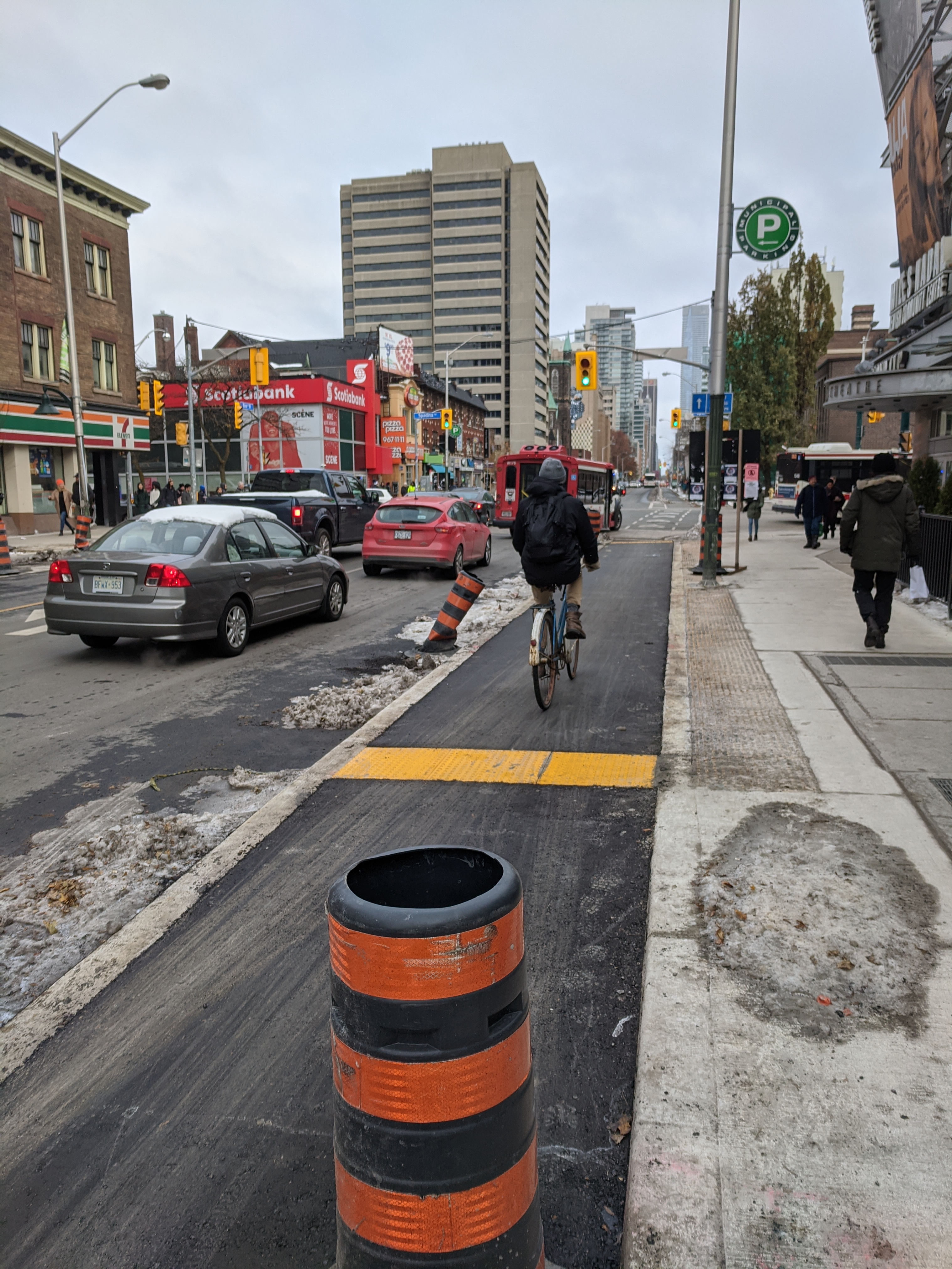 Cyclist rides on a separated cycle track on Bloor west of Spadina