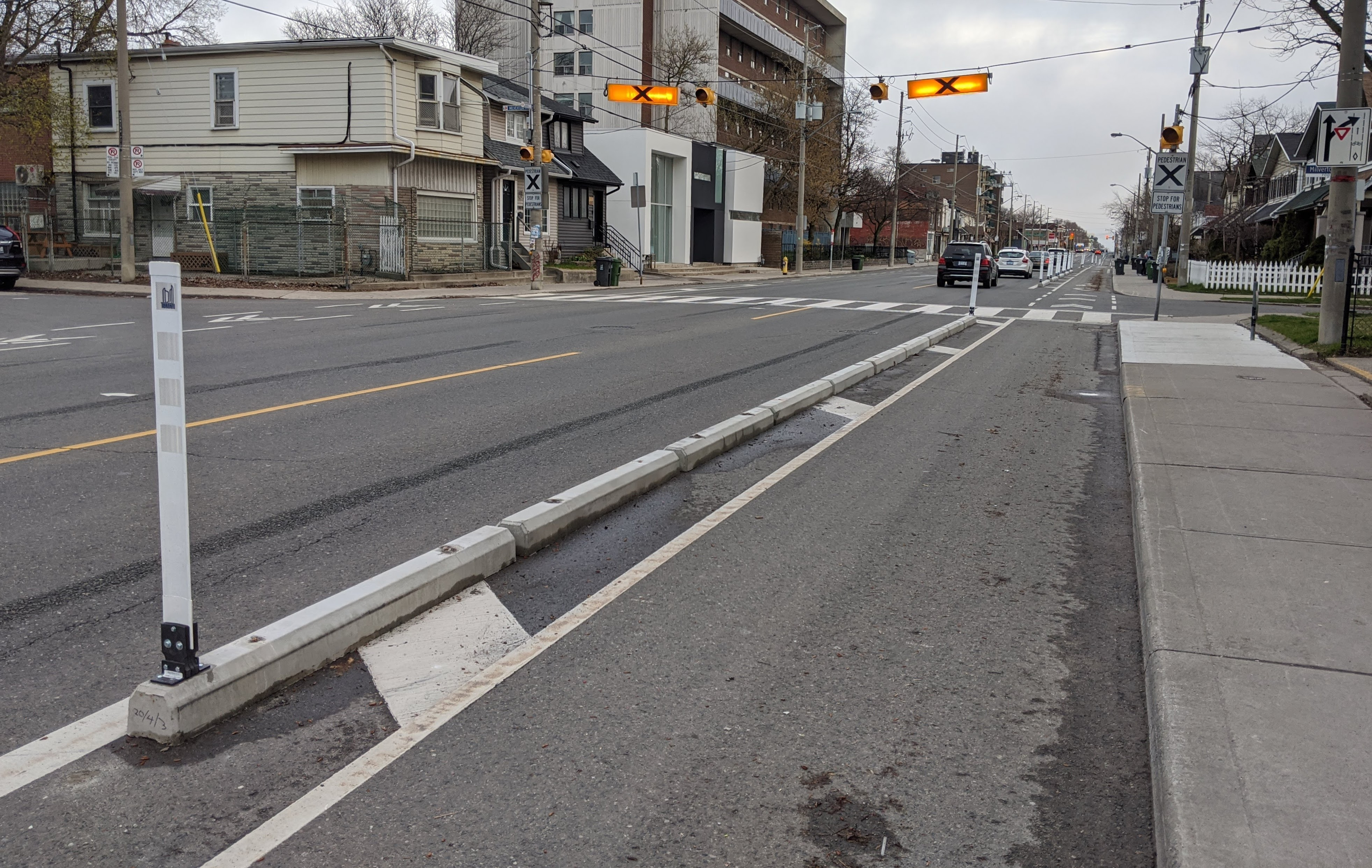 A curb separated bike lane stretches across the street