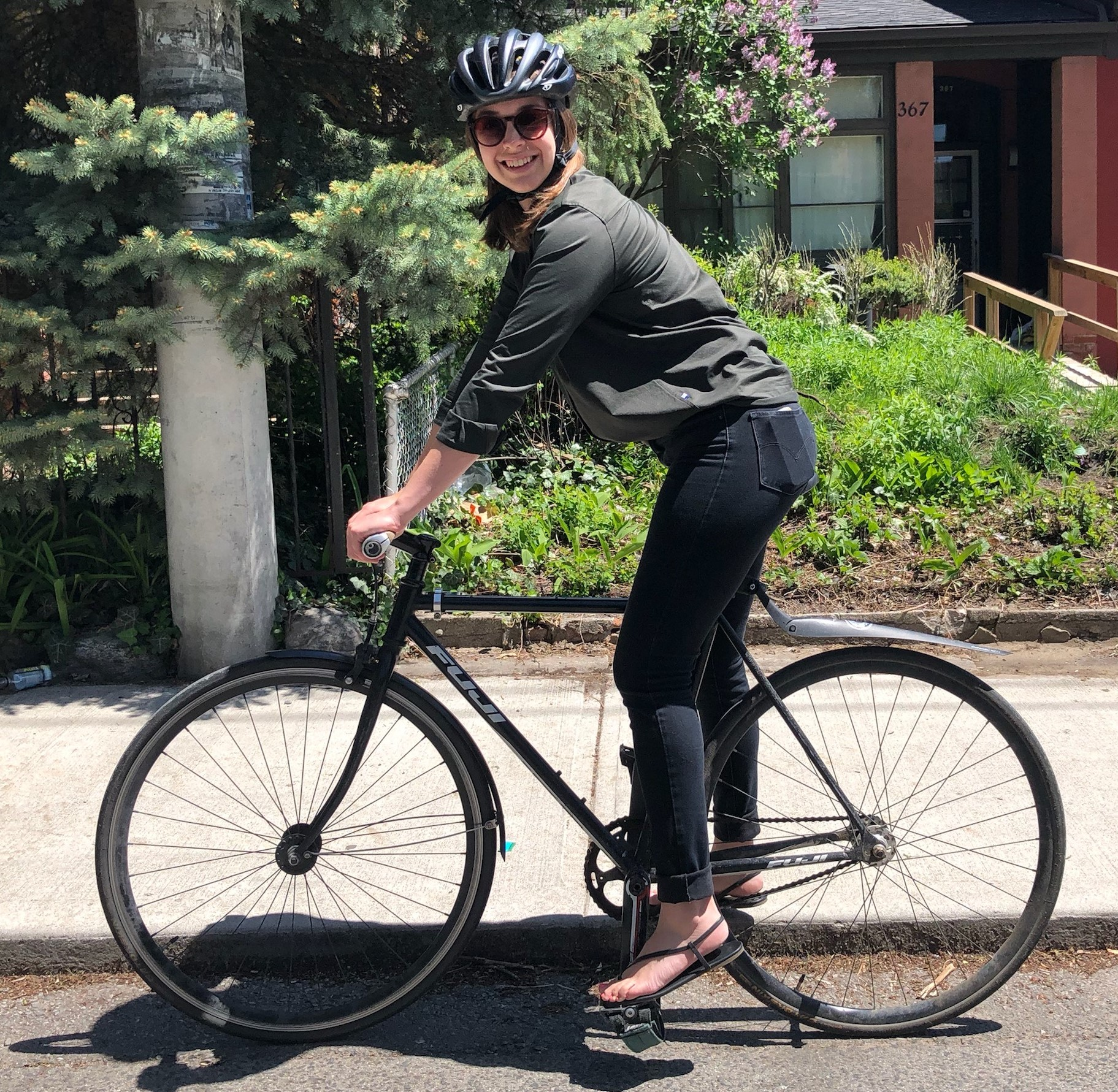 A woman sits on her bike seat. Her leg is slightly bent with the pedal all the way at the bottom.