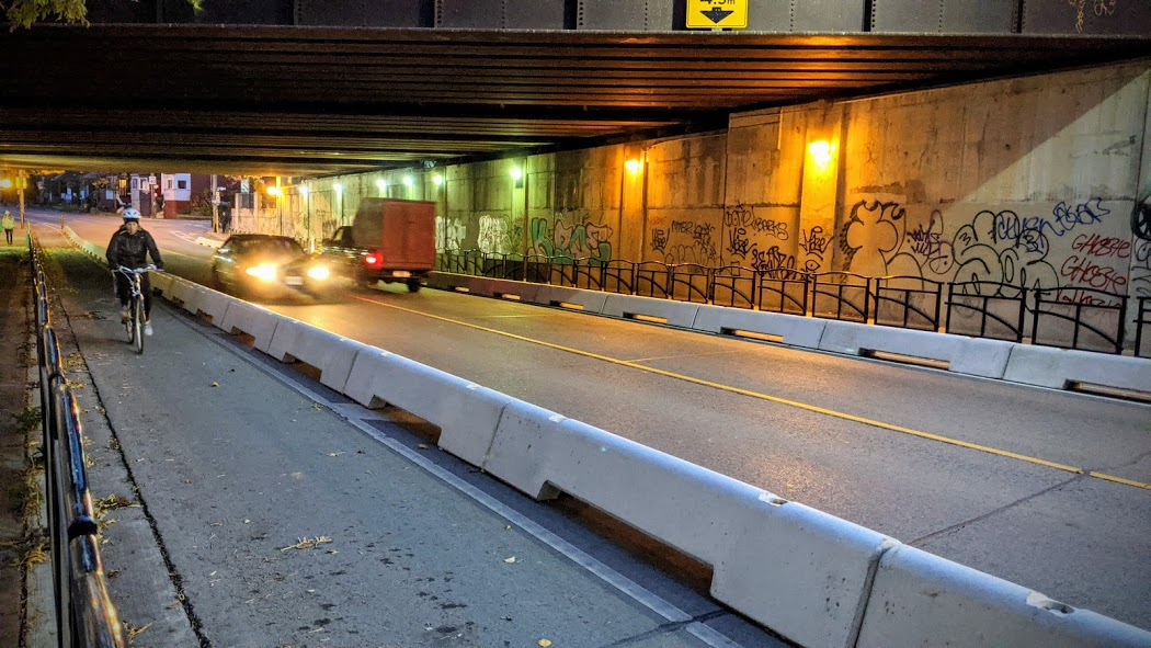 A gratified underpass is lit up at night. Concrete barriers separate cyclists from drivers.