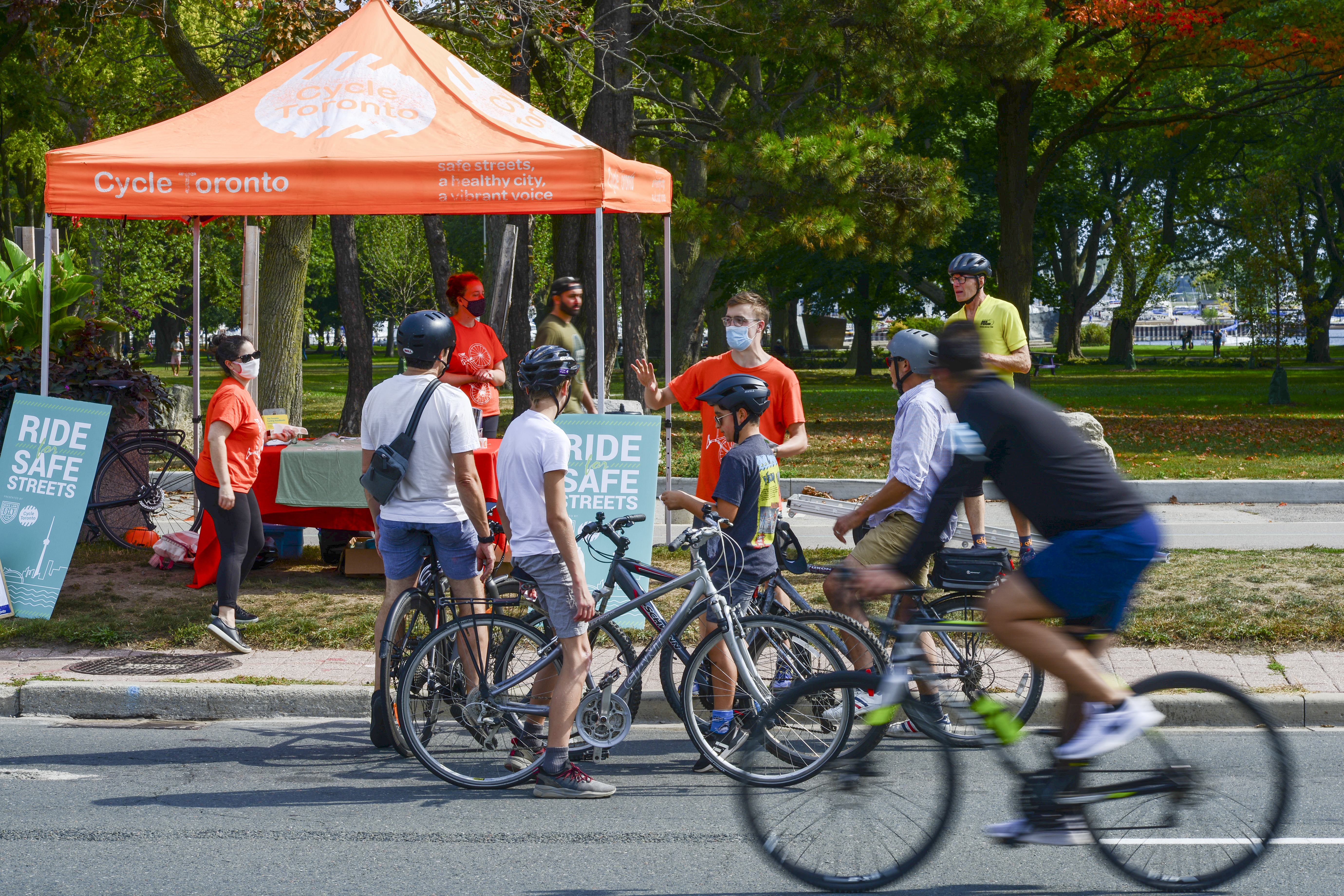 People ride past the orange Cycle Toronto tent as kids talk to volunteers and staff.