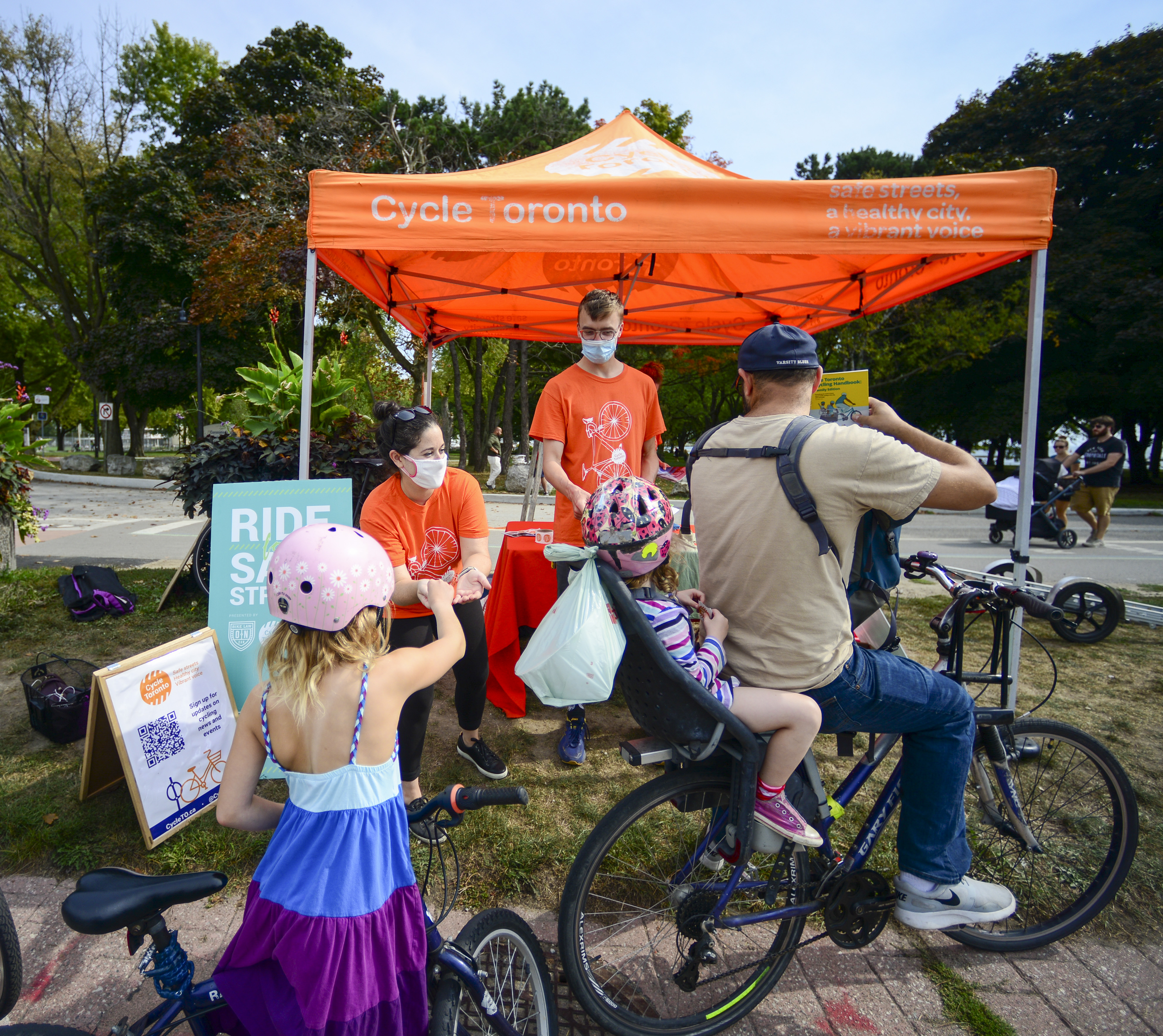 A family with young children approaches an orange Cycle Toronto tent with staff there.
