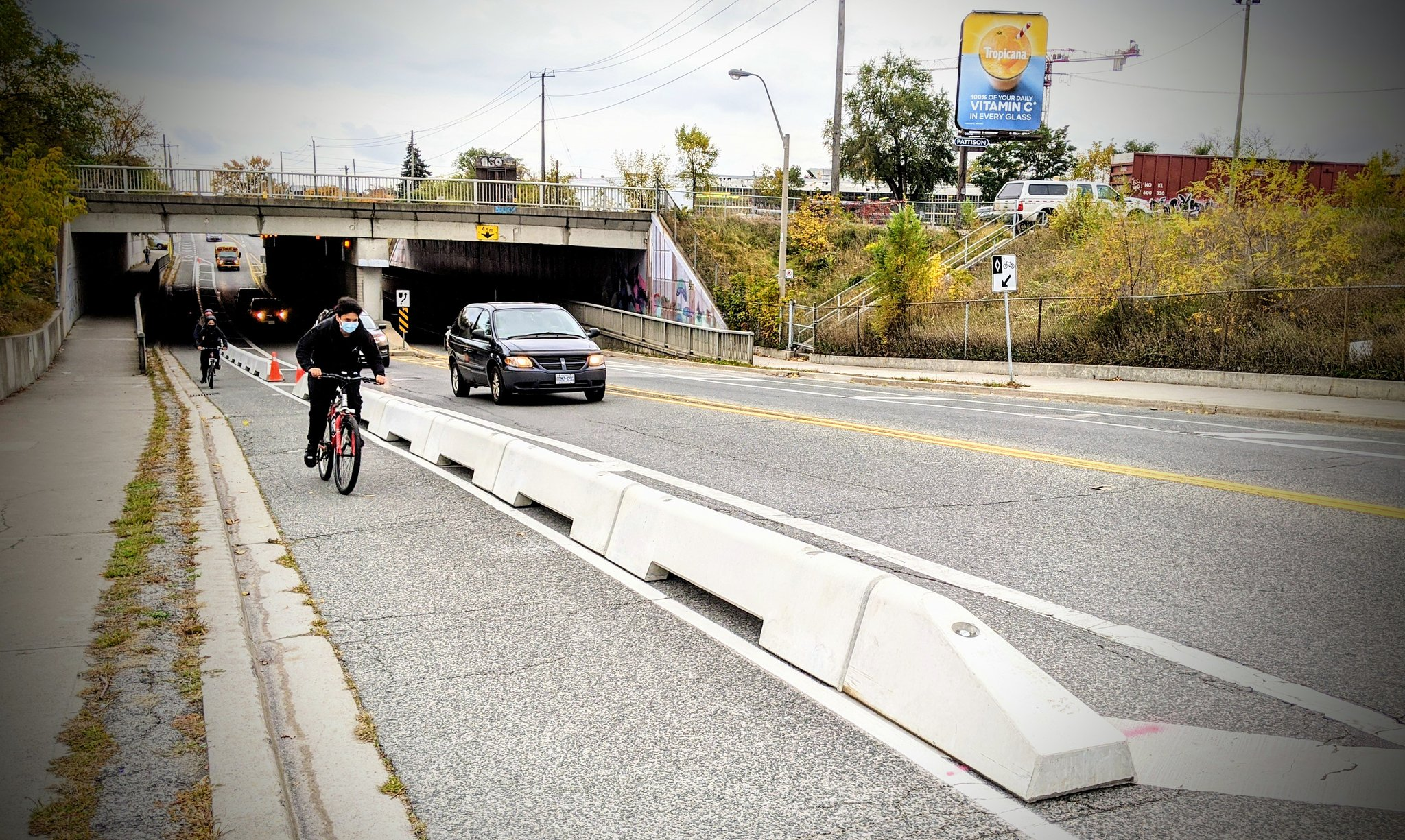 Newly installed barriers separate bike riders from cars at a rail underpass.