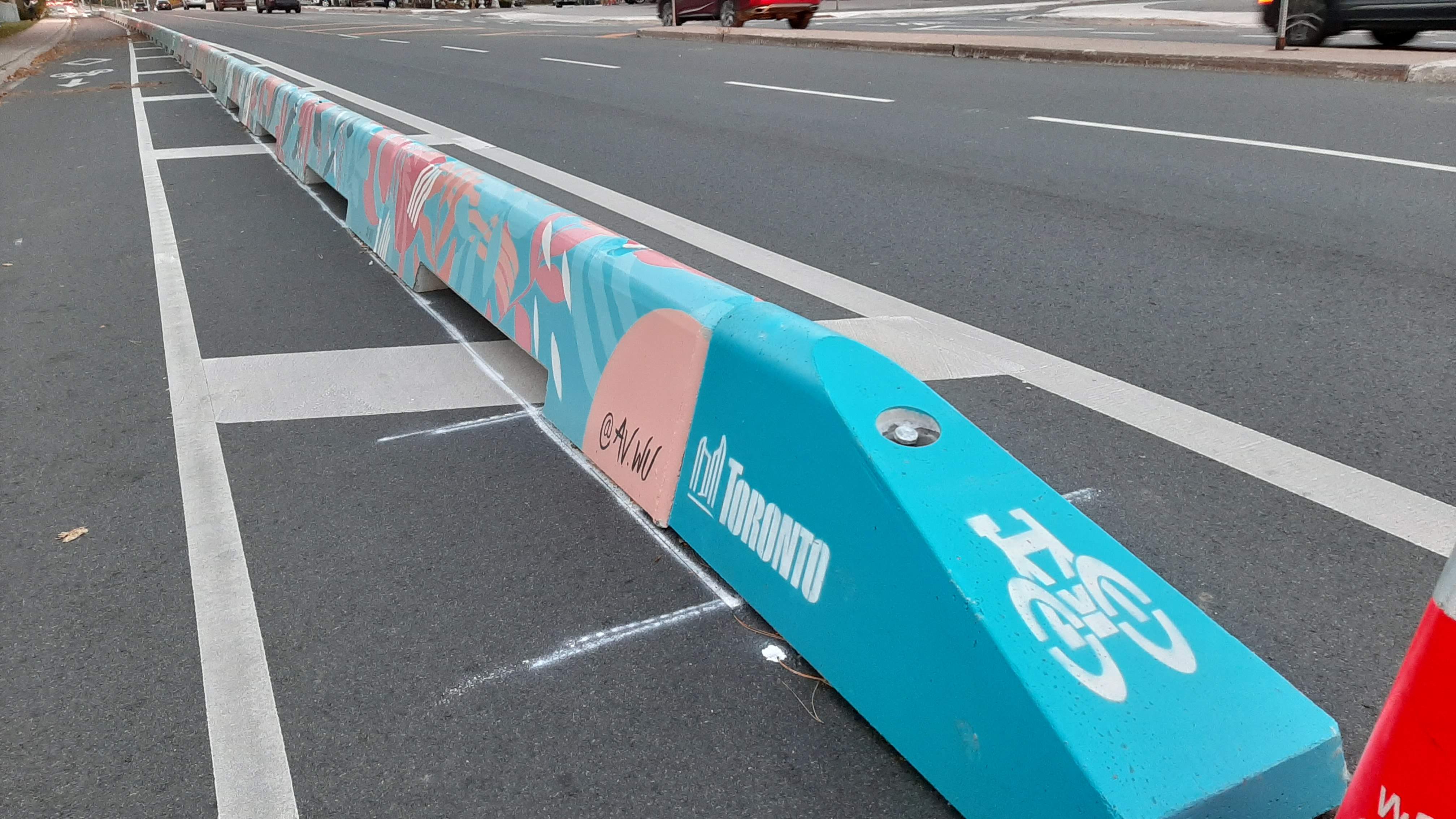 Painted in pinks, teals, and white, a low concrete wall separates a bike lane from traffic.