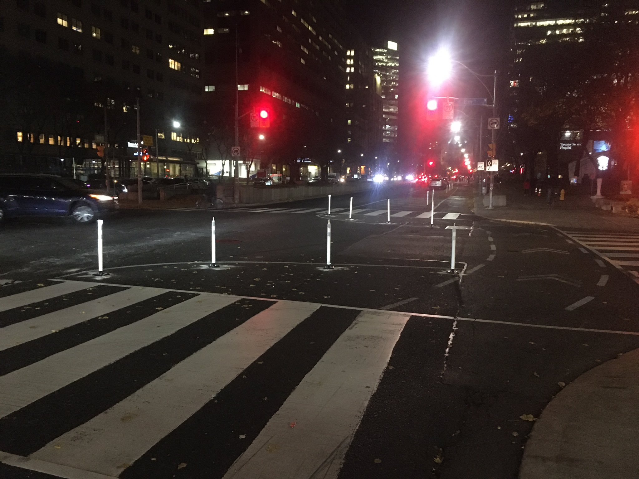 Reflective flexi-posts stand out in a dimly lit night shot. They outline the intersection beyond the crosswalk and to the left of the bike lane.