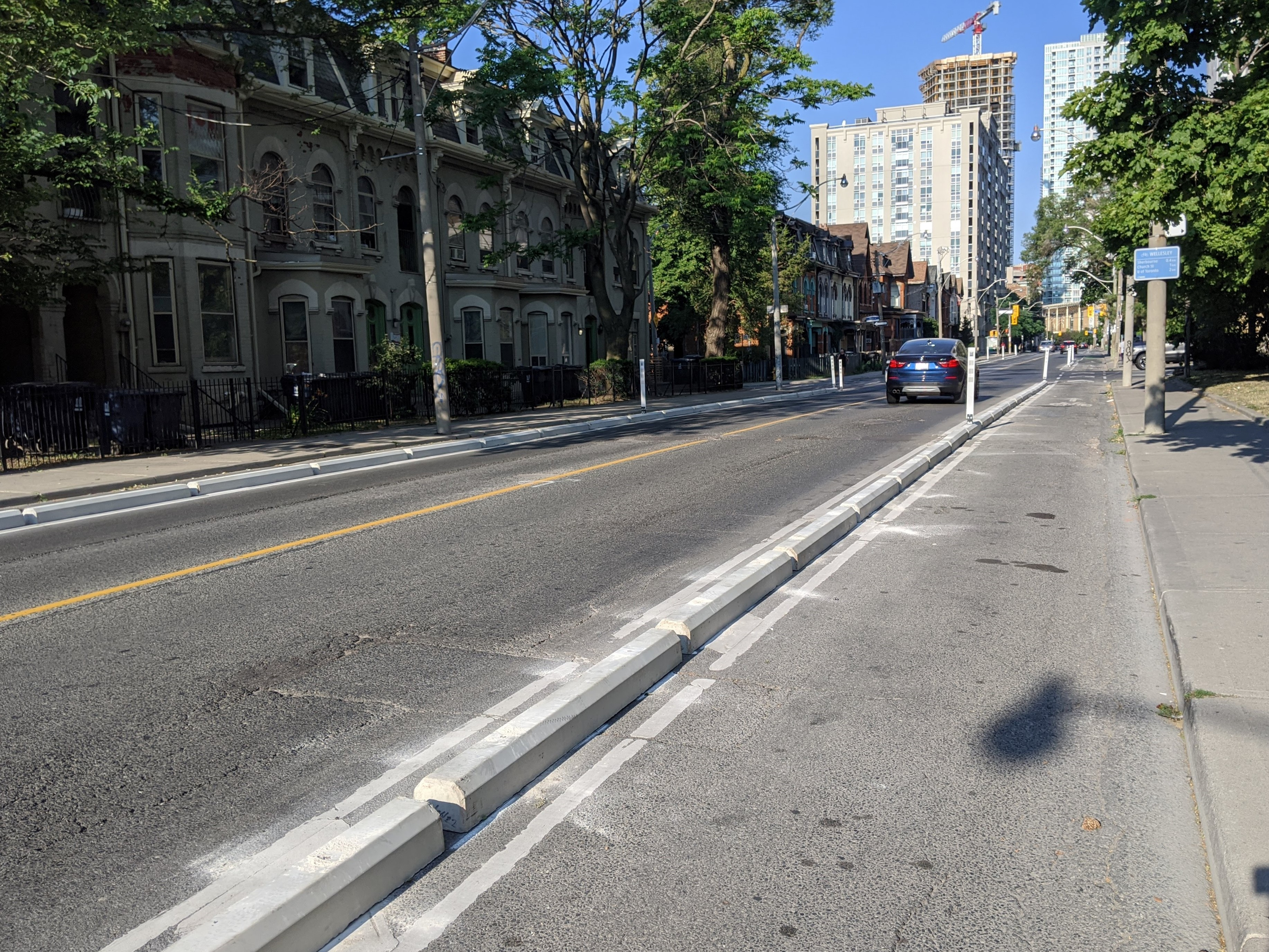 Dust surrounds freshly installed concrete curbs that separate a bike lane from a two lane road.