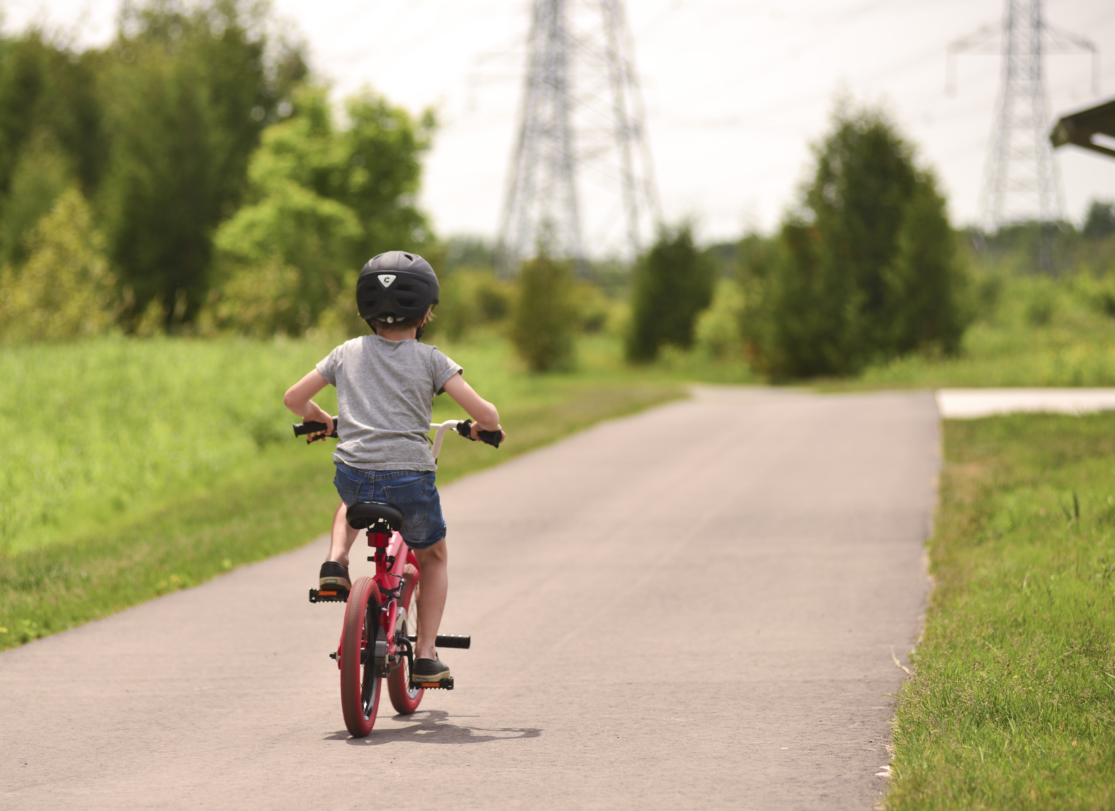A child rides a bike on their own on a paved path.
