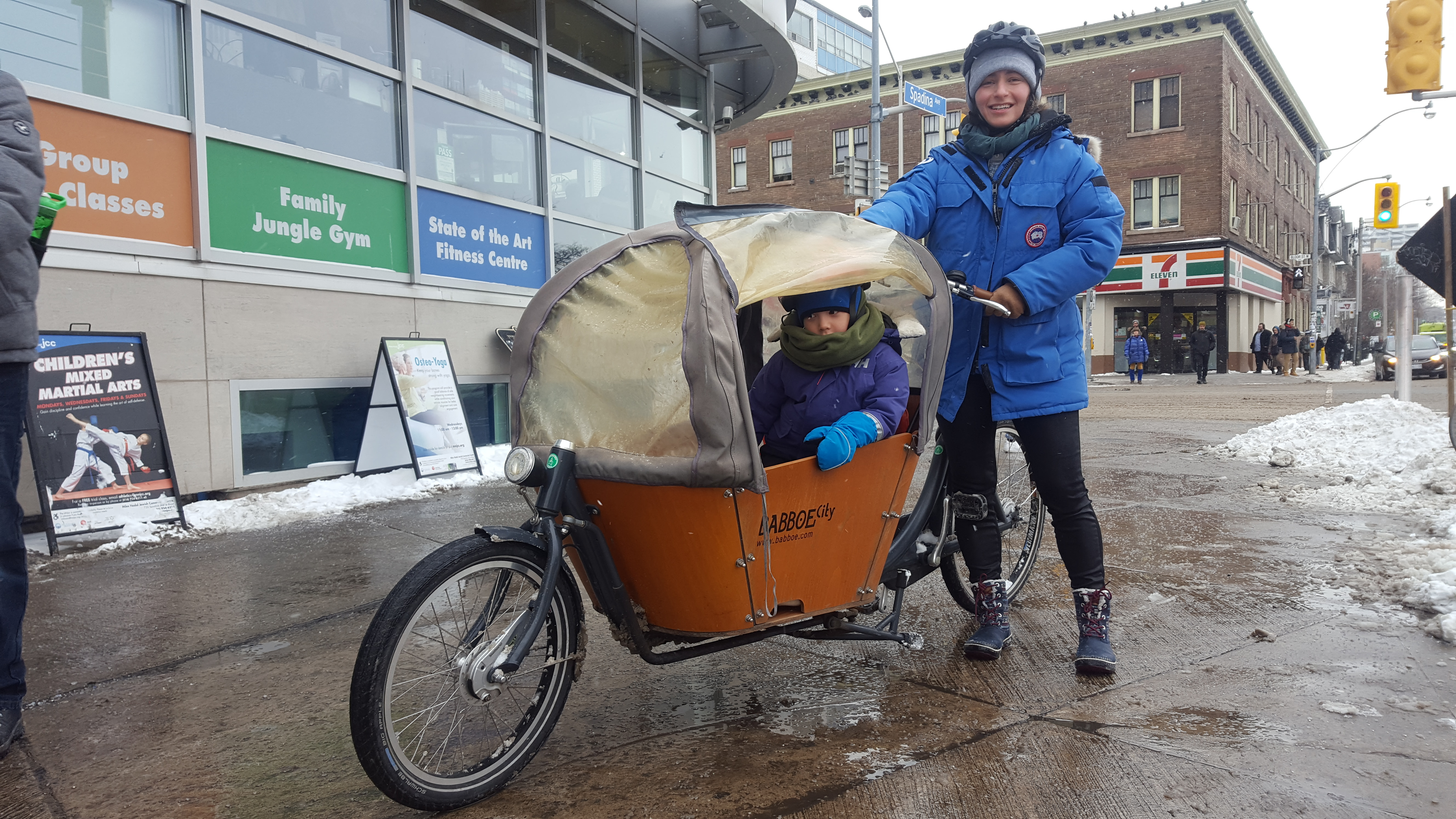 A child sits in a cargo bike with an adult standing behind them. It looks cold and wet, but the kid is warm!