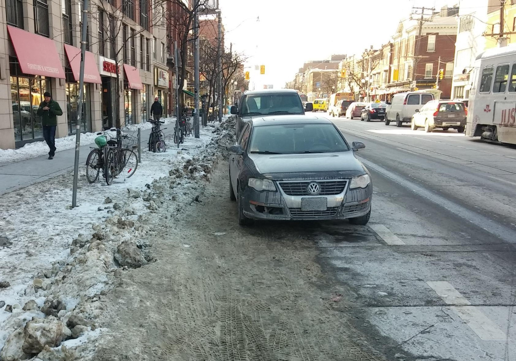 Car and snow spilling into bike lane on College Street