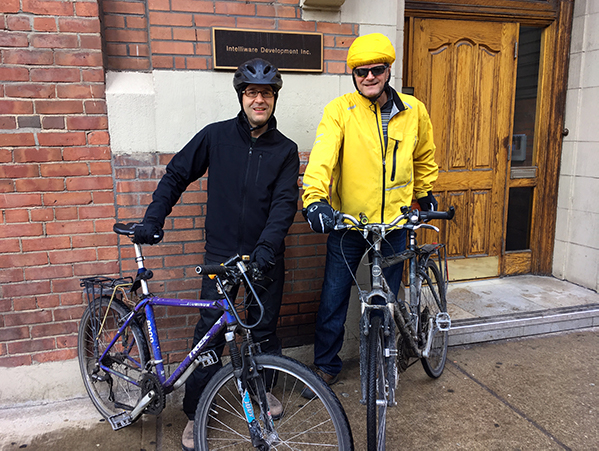 Bruno and Cesar with their bikes in front of their office building