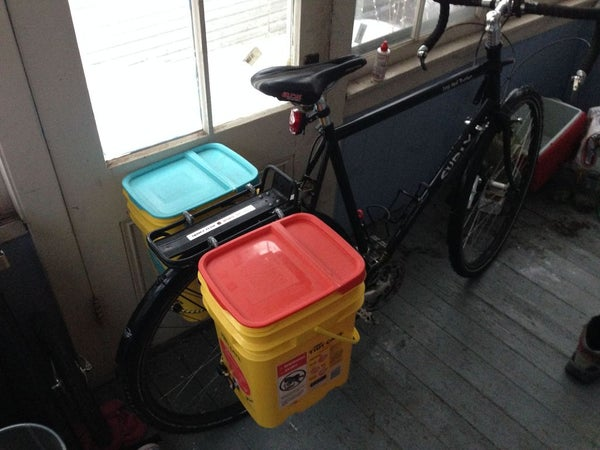 Two large kitty litter tubs attached to a bike rack