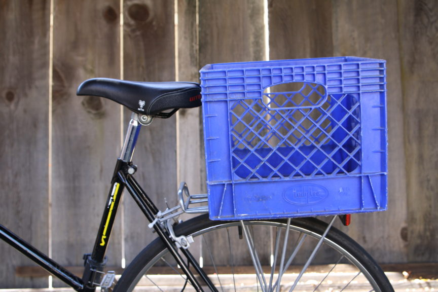 Blue milk crate attached to bike rack