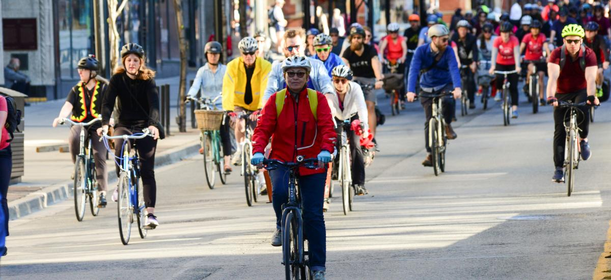 Lots of people bike down a roadway on a sunny day