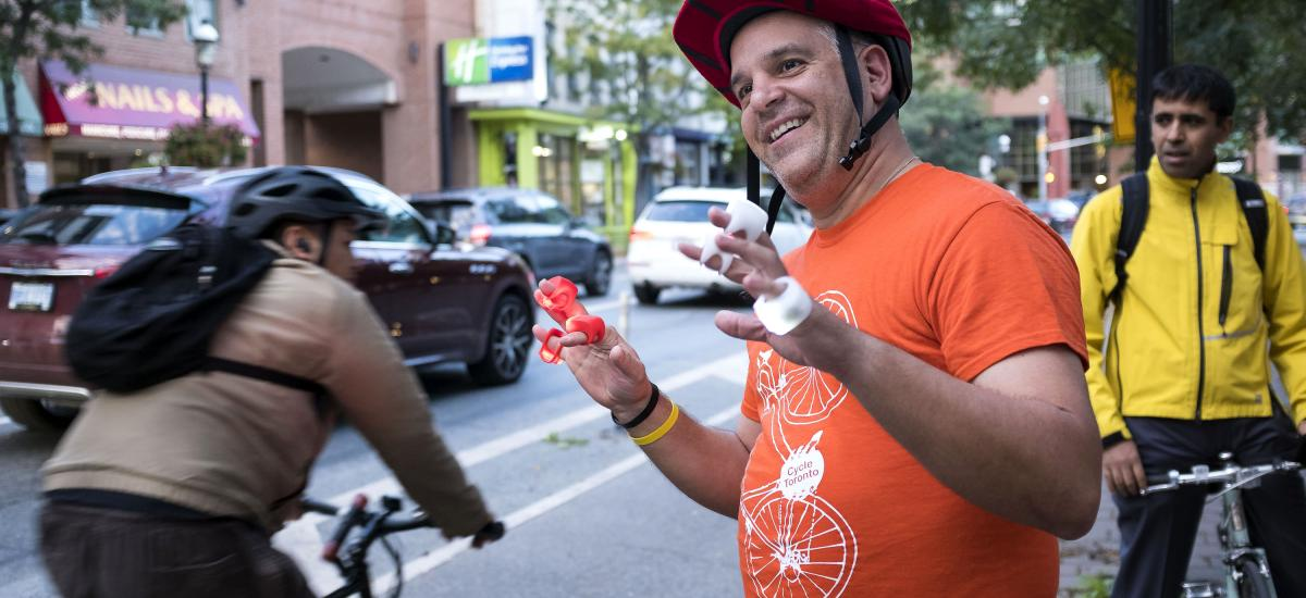 Smiling person in orange shirt hands out bike lights to passing cyclists