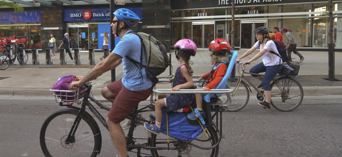Aldult riding a bike with two children on the back
