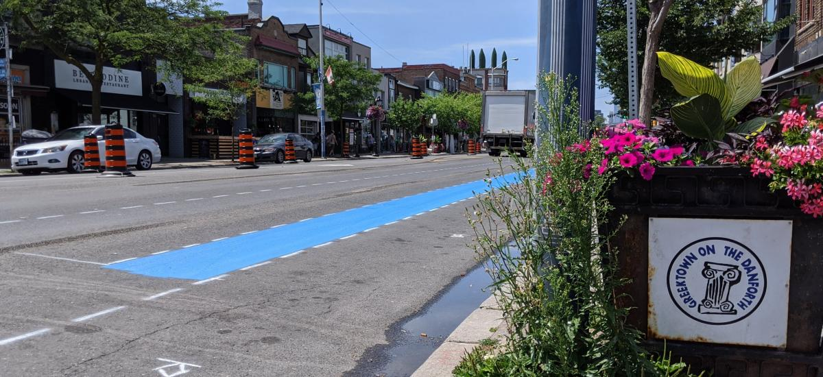 "A swath of blue paint runs through a construction zone. A sign reads ""Greektown on the Danforth"""