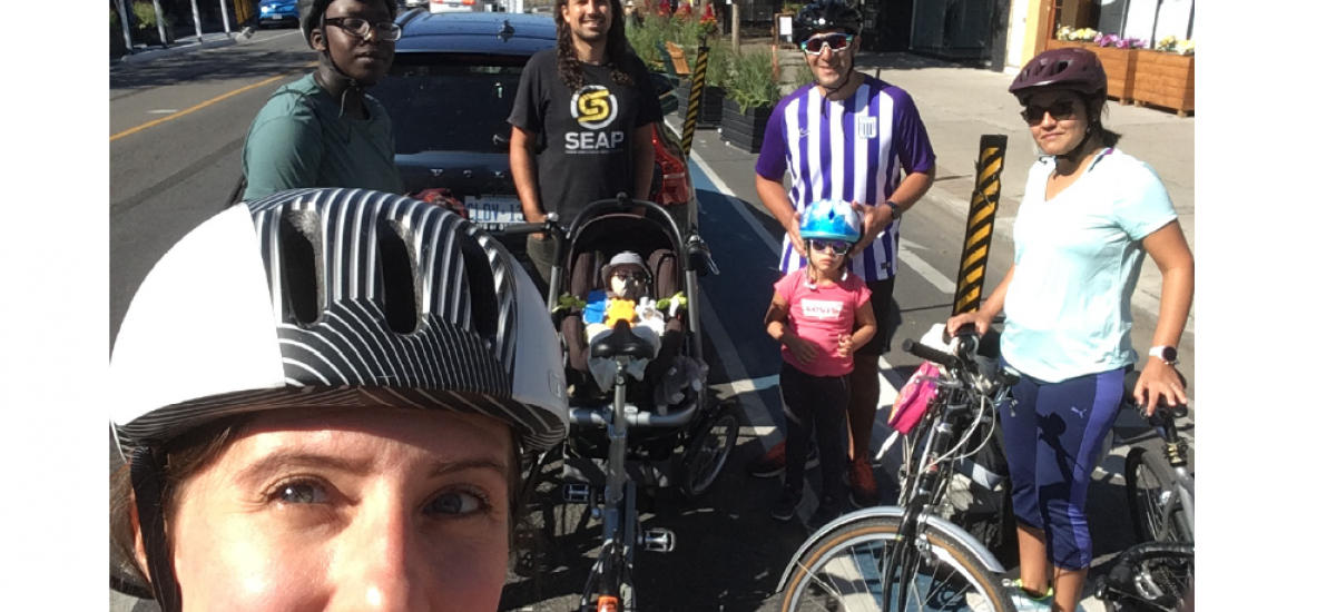 A woman poses with friends and their bikes.