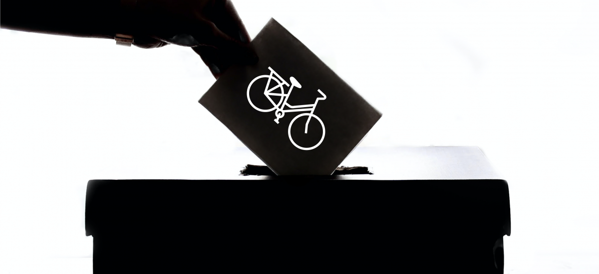 A person puts a ballot with a bike on it in a box