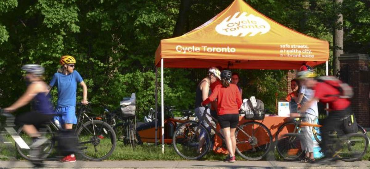 "An orange tent with ""Cycle Toronto"" written on it is set up in a park. People with bikes ride by and huddle around it."