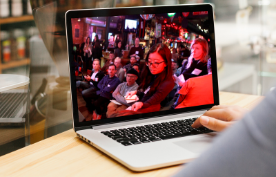 A laptop shows a photo of a Cycle Toronto member casting their vote at the 2019 Cycle Toronto Annual General Meeting. In the background, a group of people look on.