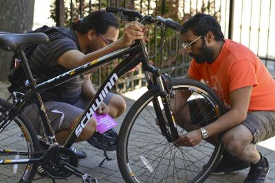 A man examines a bike wheel while his student looks on.