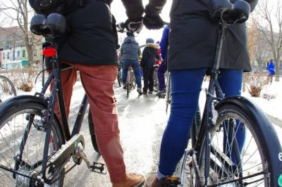 Two people stand with bikes in the snow.