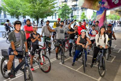 A diverse group of people pose with their bike. A man in the centre has his arms spread wide.