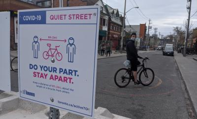 "Person with a mask on a bike beside a sign that reads ""Covid-19 Quite Street. Do your part. Stay Apart."