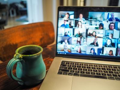 Photo of a laptop and coffee mug sitting on a table. A video call is shown on the laptop, but the faces of the participants are blurry.