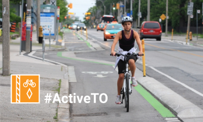 Hashtag Active T O. Person riding a bike in a protected bike lane. They're wearing a tank top and shorts.